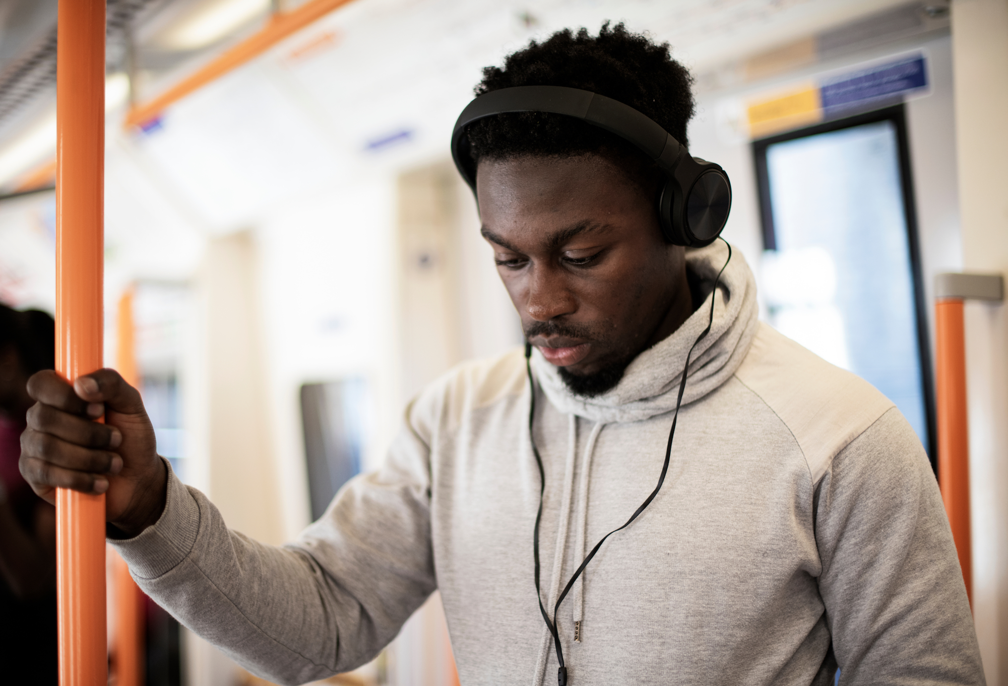 man on transit listening to a construction podcast on headphones