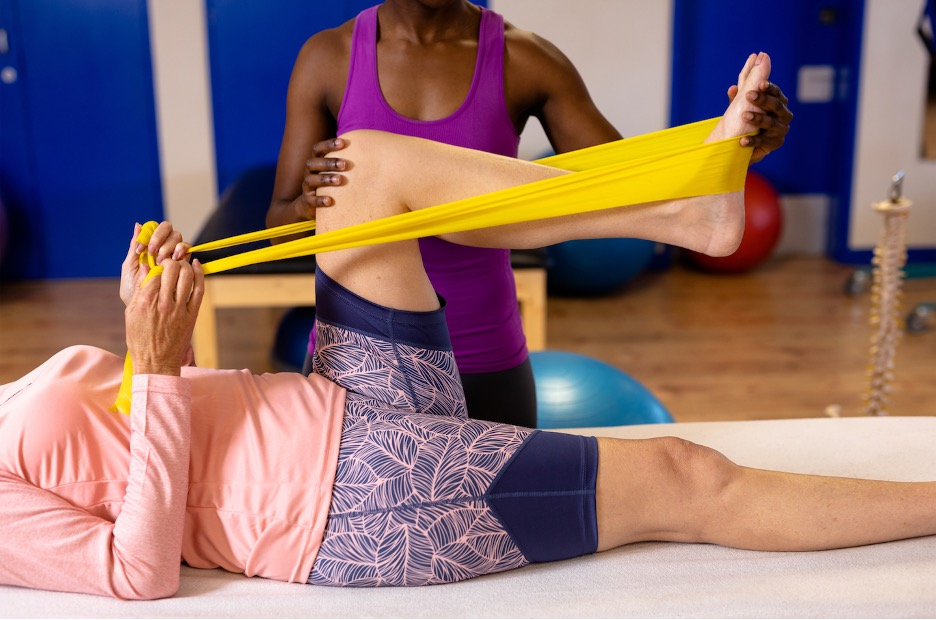 Physical therapy assistant helps a client with stretching
