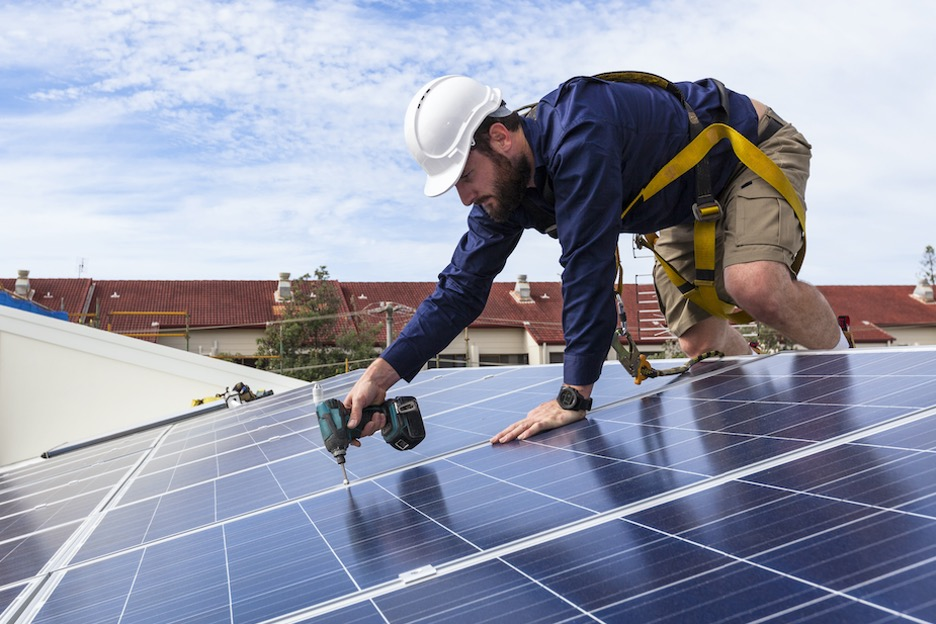 Solar energy technician works on a solar panel