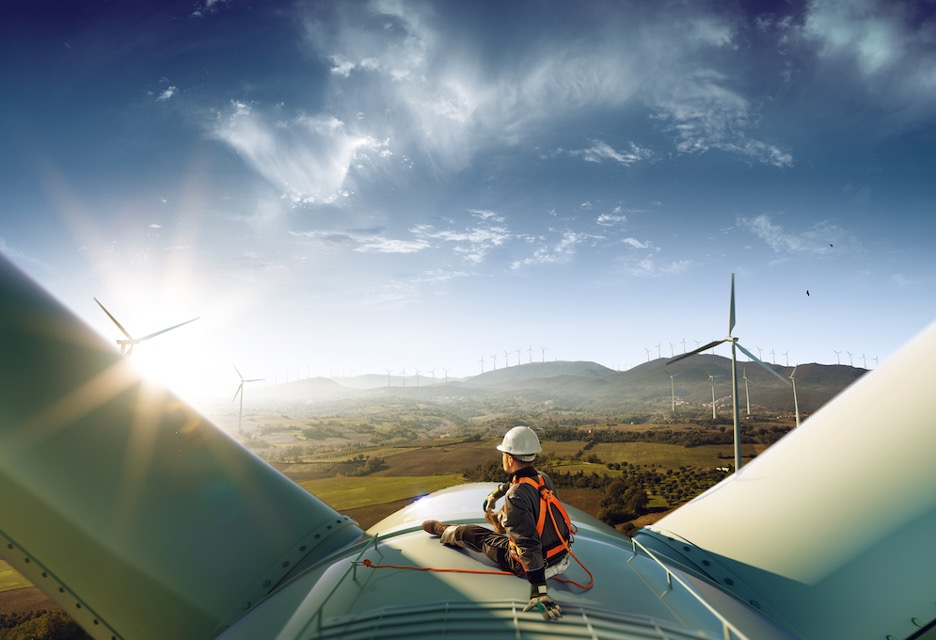 Wind turbine technician sitting on top of a wind turbine enjoying the view