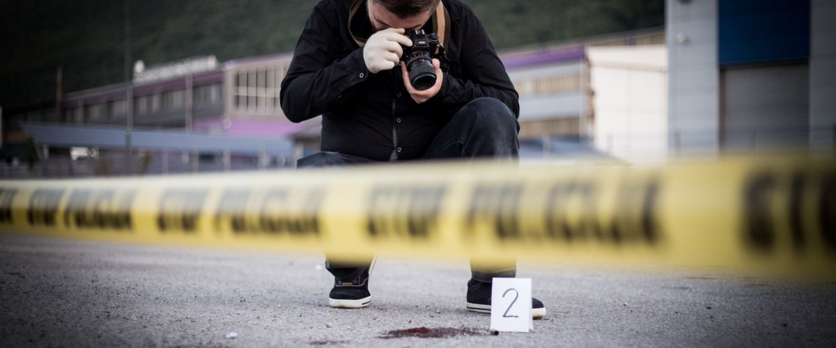 A criminal investigator takes photos at a crime scene