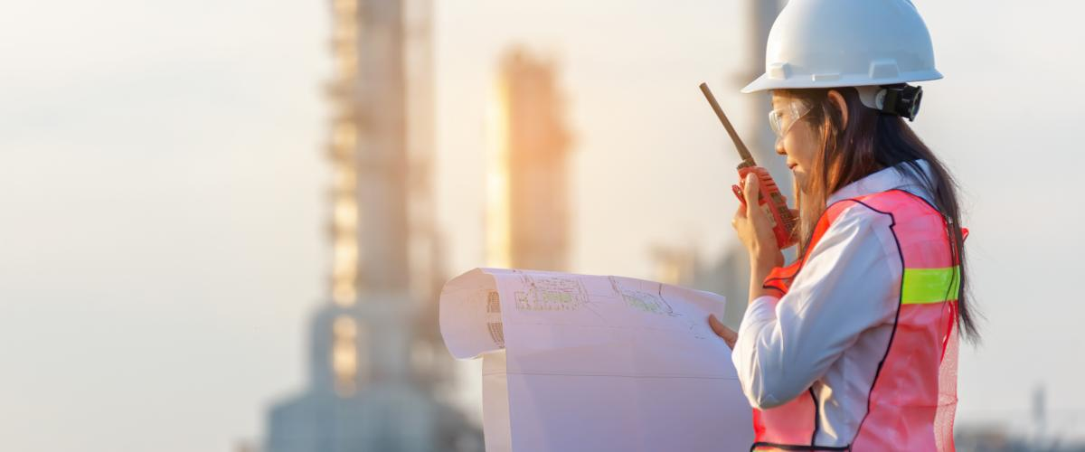 An industrial engineering technician reviews a blueprint in front of a worksite