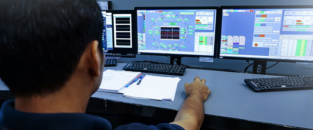 A nuclear technician monitors screens in the control room.