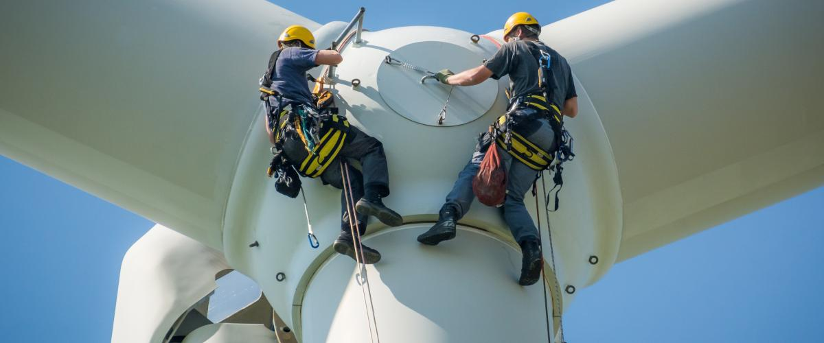 Wind turbine technicians inspect a turbine at a wind farm