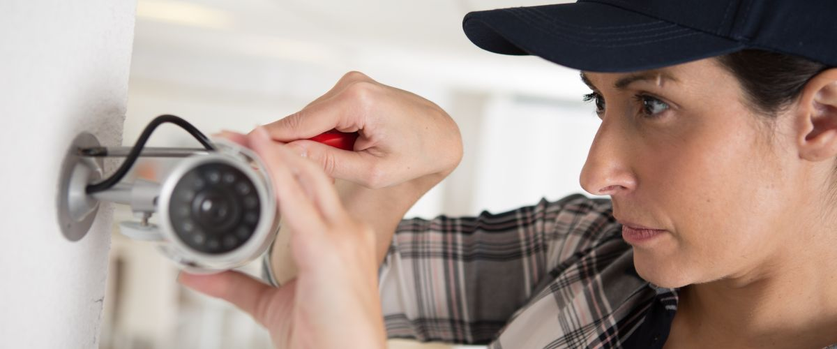 A security alarm installer adjusts a surveillance camera