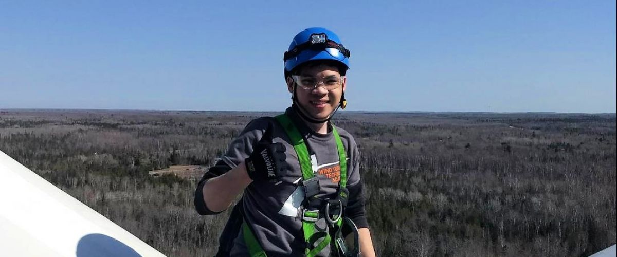 Charlie Tran, wind turbine technician ambassador, gives the thumbs-up on top of a wind turbine