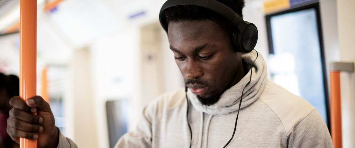 Man on train listens to construction podcast on headphones
