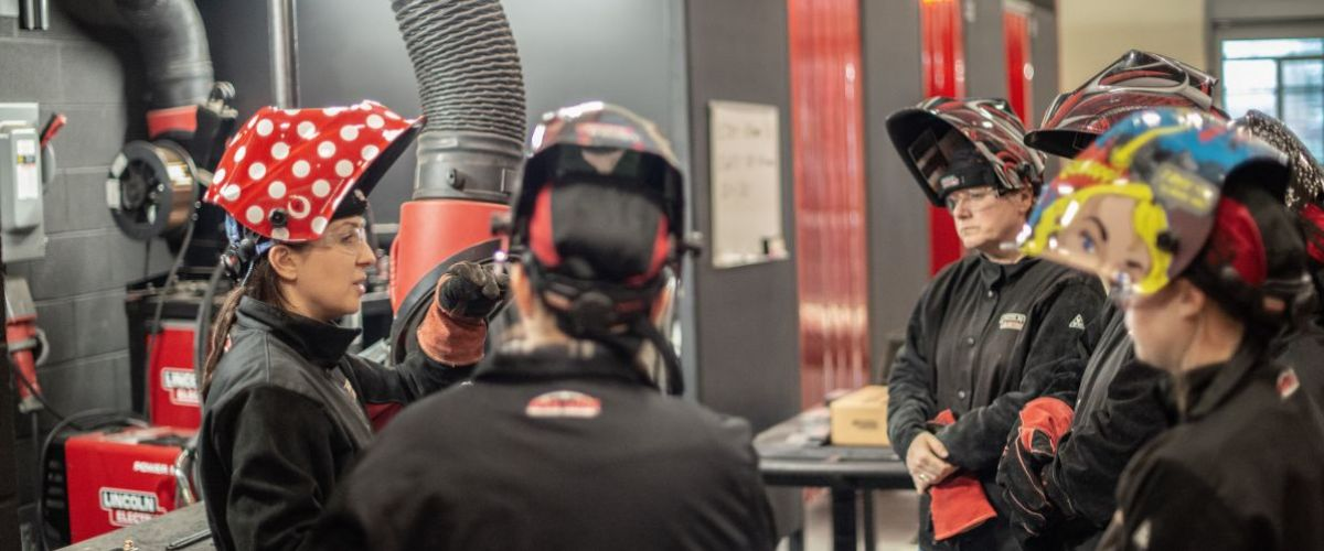 A group of women welders stand and talk with one another.