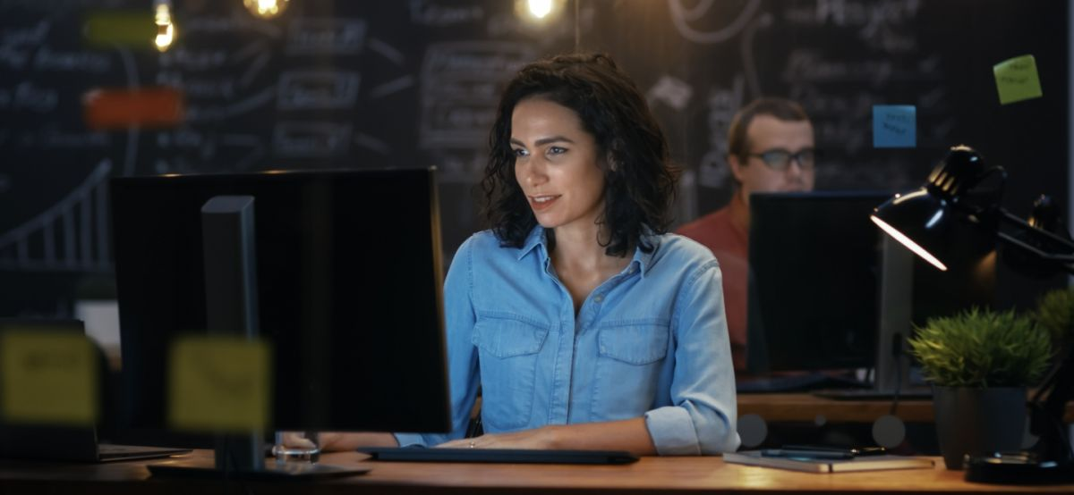 Female IT professional sits at computer