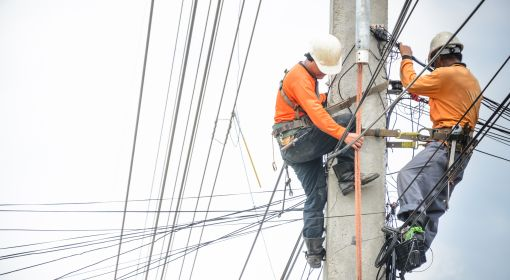 Electrical linemen work on a power line pole