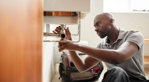 A plumber replaces a pipe fitting
