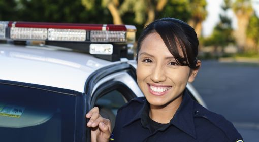 A female police officer stands by her patrol car