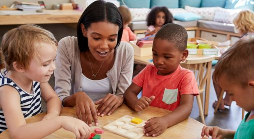 A preschool teacher helps students learn their shapes