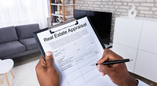 A real estate appraiser completes a form that notes the condition of a house
