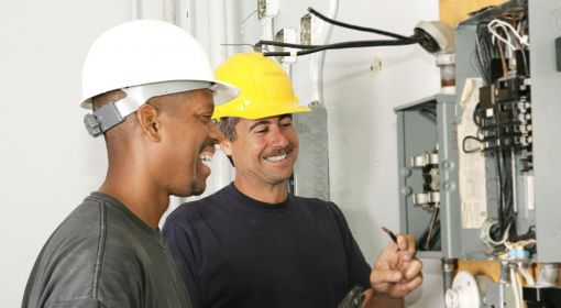 Two electricians work on an electrical panel. Electricians are among the good paying jobs that don't require a degree