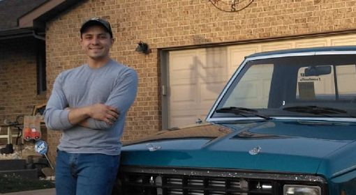 A young man stands in his driveway, leaned up against his turquoise Ford Ranger truck.
