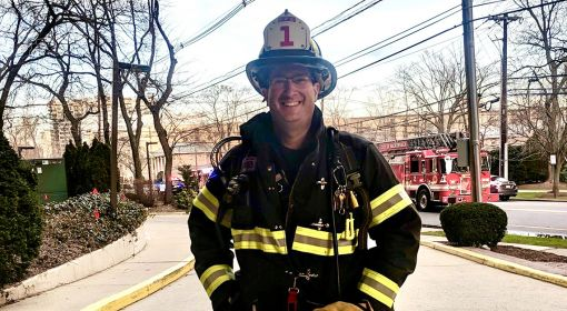 Jeffrey Kaplan, firefighter ambassador, stands in front of a firetruck in his gear