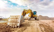 A construction equipment operator will manage an excavator to clear the way for a new road