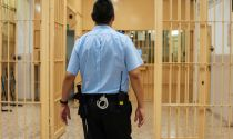 Correctional officer walks through prison aisle