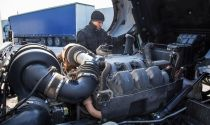 Diesel mechanic inspects a truck engine