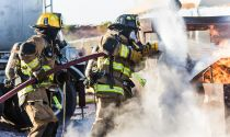 Firefighters work together in a training exercise to put out a fire