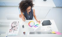A graphic designer studies a color palette at her desk