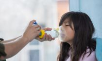 Respiratory therapist uses an inhaler to help a young girl experiencing breathing problems