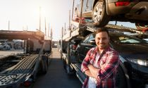 Truck driver stands in front of cars he is transporting to a dealership